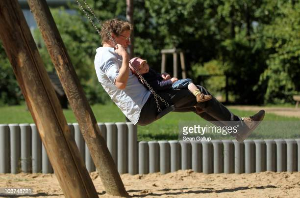 Oliver H. A married federal employee on 6-month paternity leave, swings with his twin 14-month-old daughter Lotte at a playground near his home on...