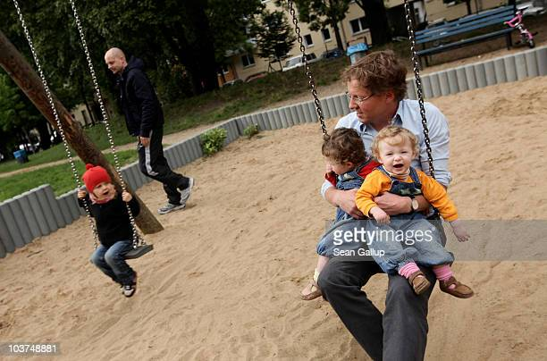 Oliver H. A married federal employee on 6-month paternity leave, swings with his twin 14-month-old daughters Lotte and Alma at a playground on August...