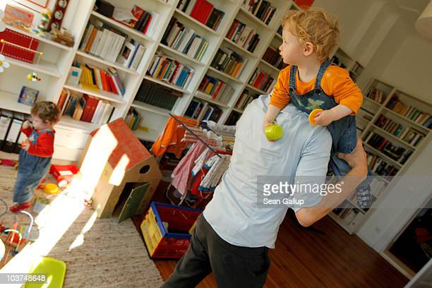 Oliver H. A married federal employee on 6-month paternity leave, prepares to clean up his twin 14-month-old daughters Lotte and Alma after breakfast...