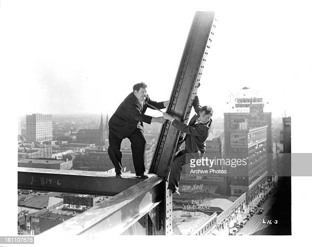 Oliver Hardy and Stan Laurel hang off a beam in a scene from the film 'Liberty' 1929
