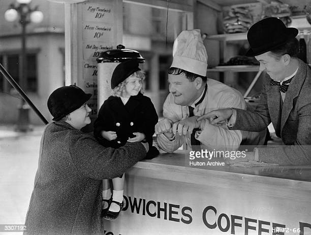 Oliver Hardy and Stan Laurel sell snack food from a van to an elderly lady and a young child, played by Jackie Lynn, in a scene from the film 'Pack...