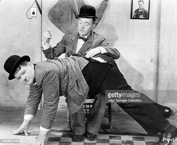 Oliver Hardy lays atop Stan Laurel's lap as Stan fixes a tear in his trousers in Hollywood Party