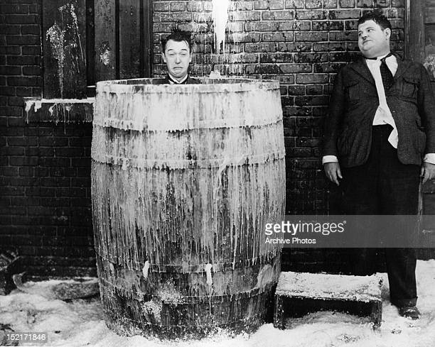 Oliver Hardy looking over at Stan Laurel in a barrel in a scene from the film 'Below Zero' 1930