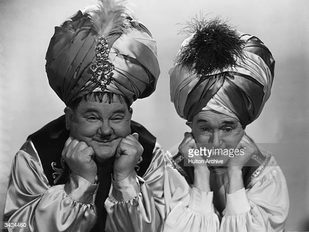 Oliver Hardy the ample American comedian, with Stan Laurel , his British born sidekick, wearing turbans as they appear in 'A-Haunting We Will Go',...