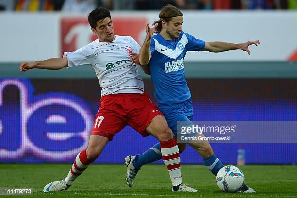 Oliver Hein of Regensburg challenges Gaetan Krebs of Karlsruhe during the Second Bundesliga relegation match between Karlsruher SC and Jahn...