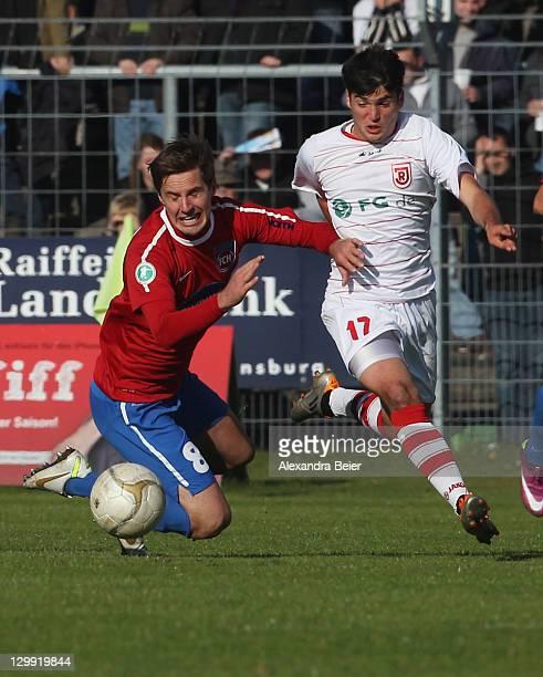 Oliver Hein of Regensburg fouls Sandro Sirigu of Heidenheim during the third league match between Jahn Regensburg and 1. FC Heidenheim at Jahnstadion...