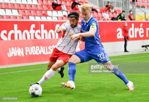 Oliver Hein of Regensburg is challenged by Fabian Holland of Darmstadt during the Second Bundesliga match between SSV Jahn Regensburg and SV...
