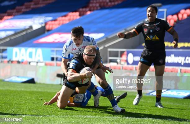Oliver Holmes of Castleford scores a first half try past Zane Tetevano of Leeds during the Betfred Super League match between Leeds Rhinos and...