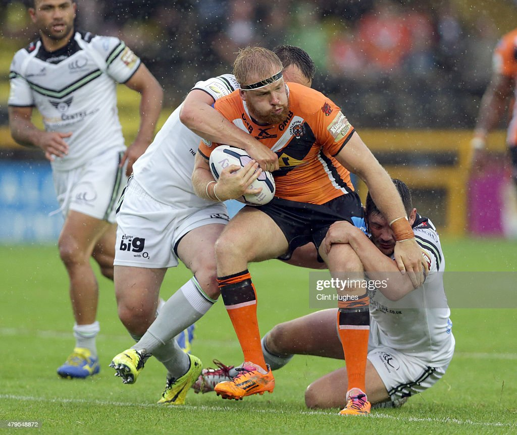 Oliver Holmes (C) of Castleford Tigers is tackled by Eamon O'Carroll (L) and Chris Clarkson (R) of Widnes Vikings during the First Utility Super League match between Castleford Tigers and Widnes Vikings at The Jungle on July 5, 2015 in Castleford, England.