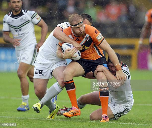 Oliver Holmes of Castleford Tigers is tackled by Eamon O'Carroll and Chris Clarkson of Widnes Vikings during the First Utility Super League match...