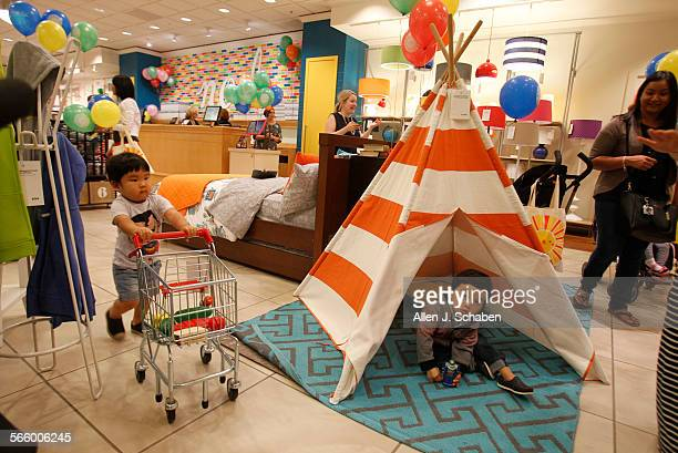 Oliver Hong left of Aliso Viejo pushes his mini shopping cart with toys as Owen Lee of Irvine plays under a teepee at the Land of Nod a children's...