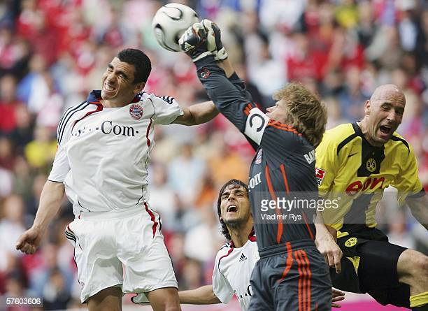 Oliver Kahn punches the ball as his team mates Lucio and Roque Sant Cruz of Bayern defend Jan Koller of Dortmund during the Bundesliga match between...