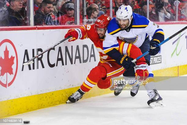 Oliver Kylington of the Calgary Flames chases the puck against Patrick Maroon of the St Louis Blues during an NHL game at Scotiabank Saddledome on...