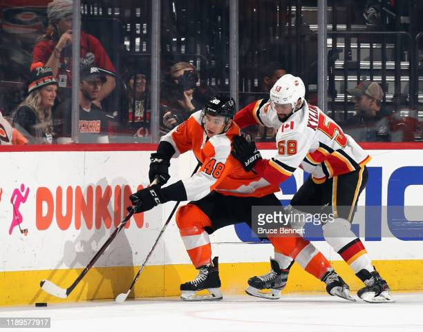 Oliver Kylington of the Calgary Flames keeps a hold on Morgan Frost of the Philadelphia Flyers during the first period at the Wells Fargo Center on...