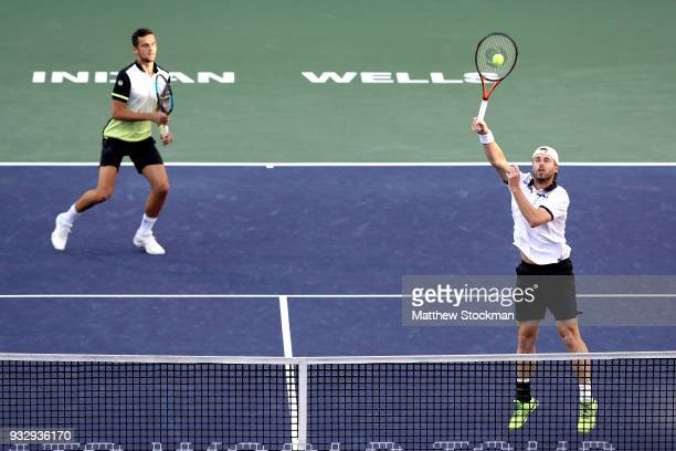 Oliver Marach of Austria returns a shot to John Isner and Jack Sock while playing with Mate Pavic of Croatia during the doubles semifinals of the BNP...