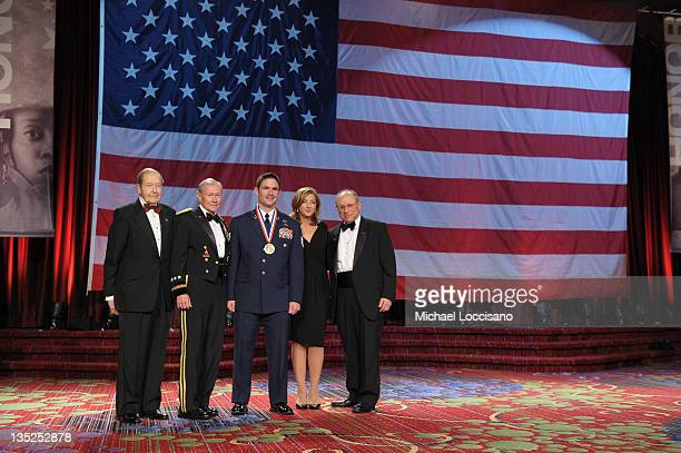 Oliver Mendell Martin E Dempsey Airman of the year Michael Brait Chris Jansing and Myron Berman pose onstage at the 50th USO Armed Forces gala Gold...