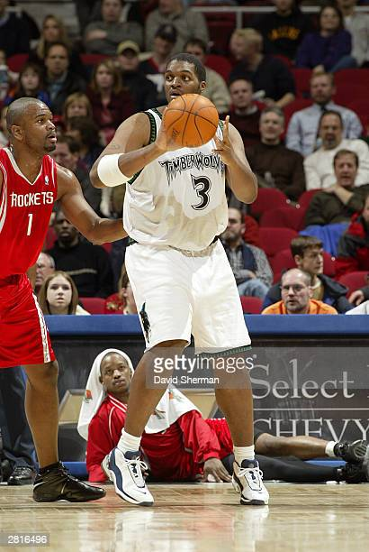 Oliver Miller of the Minnesota Timberwolves looks to pass the ball against Alton Ford of the Houston Rockets on December 16 2003 at Target Center in...