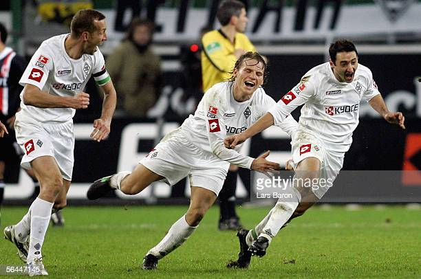 Oliver Neuville of Monchengladbach celebrates scoring his second goal with team mates Jeff Strasser and Eugen Polanski during the Bundesliga match...