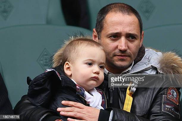 Oliver Neuville sits with his child on the tribune during the Bundesliga match between Borussia Moenchengladbach and Hannover 96 at Borussia Park...