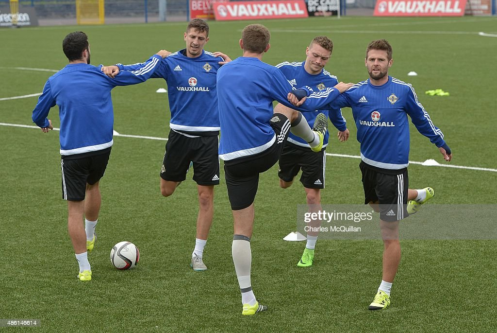 Oliver Norwood (R) and Craig Cathcart (2nd L) of Northern Ireland limber up with team mates as the international football squad train on Bangor F.C's plastic pitch on September 1, 2015 in Bangor, Northern Ireland. Northern Ireland travel to face the Faroe Islands in a Euro 2016 Group F qualifiying game in Torshavn on Friday evening.