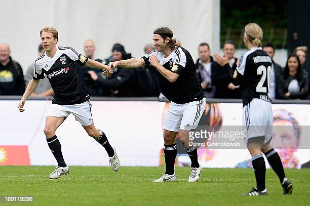 Oliver Pocher celebrates with teammate Torsten Frings during the 'Kicken fuer den guten Zweck' event at Sportpark Hoehenberg on May 20 2013 in...