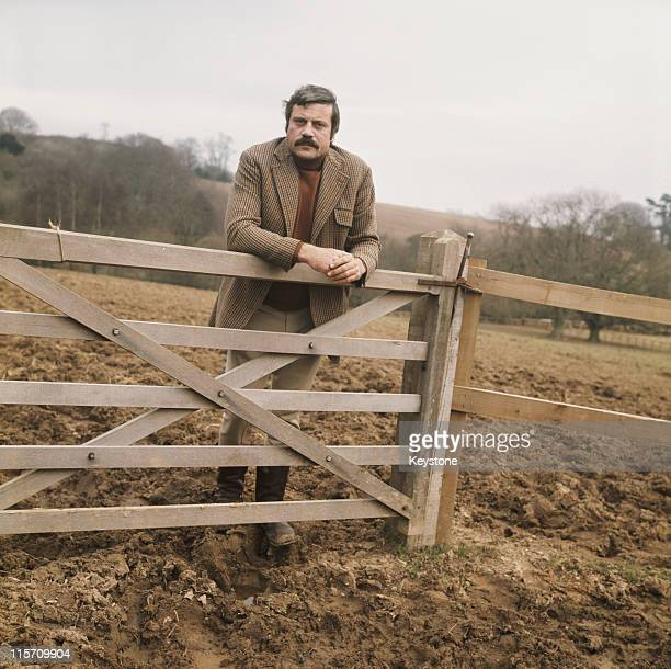 Oliver Reed , British actor, wearing a tweed jacket and wellington boots while leaning on a five-bar gate in a field, Great Britain, circa 1975.