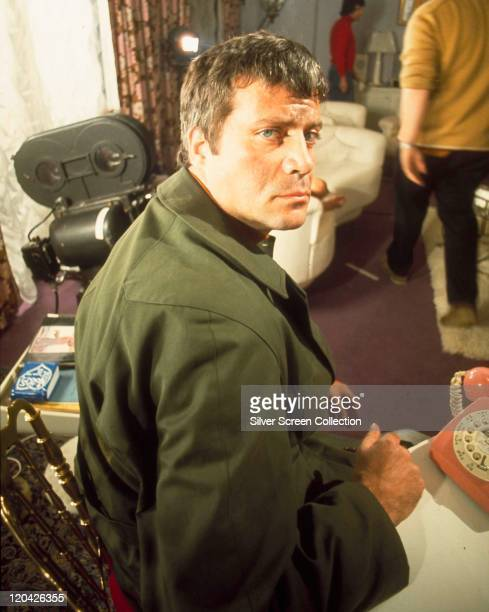 Oliver Reed looking over his shoulder wearing a green coat on the set of a film with a movie camera in the backround circa 1970