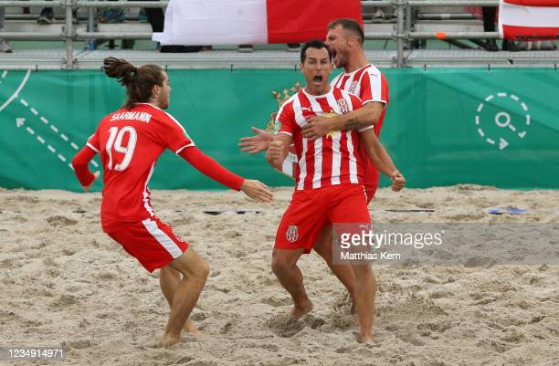 Oliver Romrig of Duesseldorf celebrates with teammates after scoring a goal during the German Beachsoccer Championship semi final match between...
