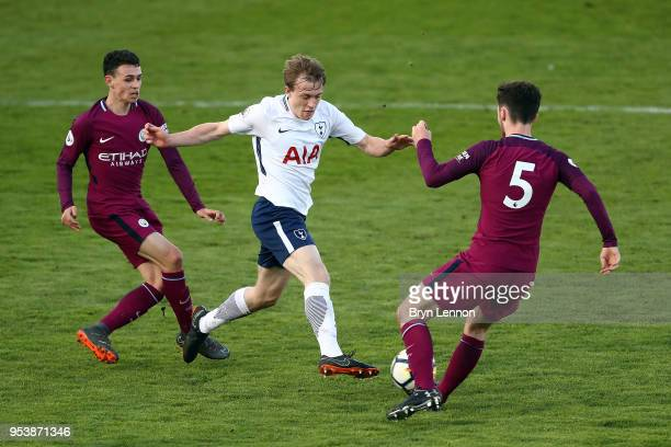 Oliver Skipp of Tottenham Hotspur is challenged by Phil Foden and Ed Francis of Manchester City during the Premier League 2 match between Tottenham...