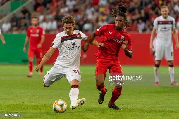 Oliver Sorg of FC Nuernberg and Caniggia Ginola Elva of FC Ingolstadt battle for the ball during the DFB Cup first round match between SV Sandhausen...