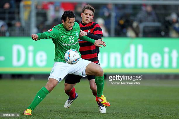 Oliver Sorg of Freiburg fights for the ball with Claudio Pizzaro of Bremen during the Bundesliga match between SC Freiburg and Werder Bremen at Mage...
