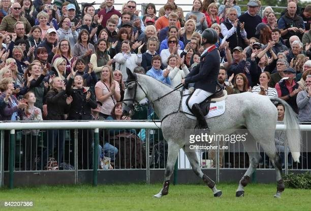 Oliver Townend of Great Britain riding Ballaghmor Class celebrates winning the Land Rover Burghley Trophy by throwing his gloves into the crowd...