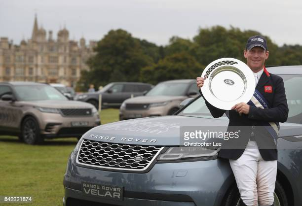 Oliver Townend of Great Britain riding Ballaghmor Class poses for the camera's with the Land Rover Burghley Trophy after his victory during Day Four...