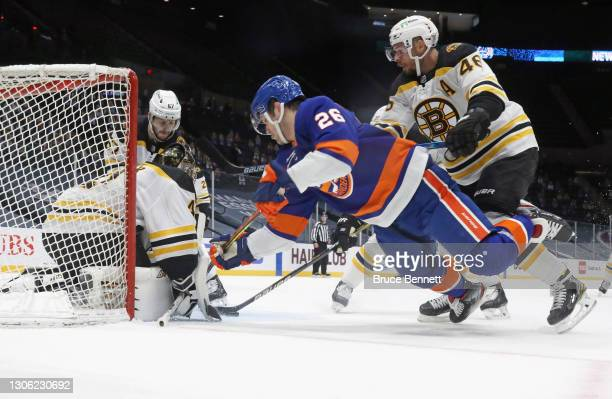 Oliver Wahlstrom of the New York Islanders is checked by David Krejci of the Boston Bruins at the Nassau Coliseum on March 09, 2021 in Uniondale, New...