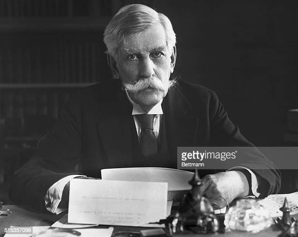 Oliver Wendell Holmes , Associate Justice of the Supreme Court, is shown seated at his desk. Photograph.