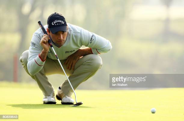 Oliver Wilson of England lines up a put on the 2nd hole during the first round of the BMW Asian Open at the Tomson Shanghai Pudong Golf Club on April...