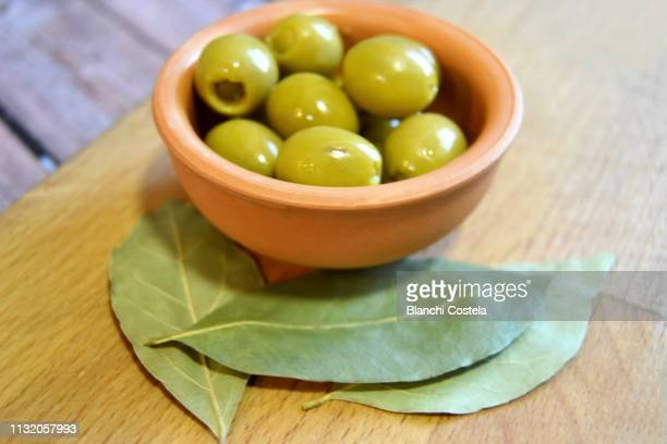 olives and bay leaves - green olive stock photos and pictures