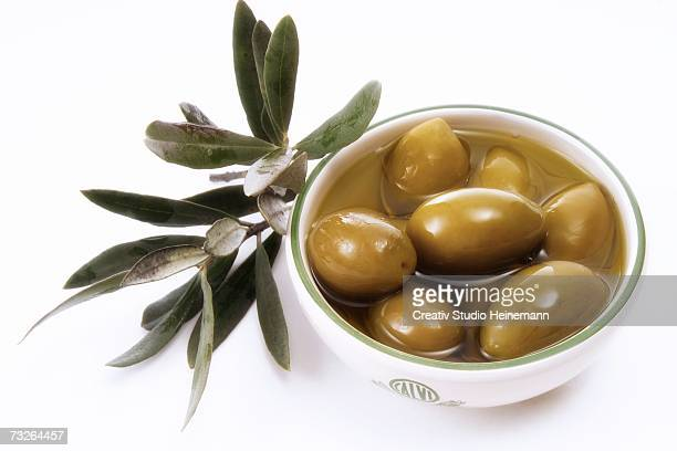 Olives in bowl and leaves, close-up