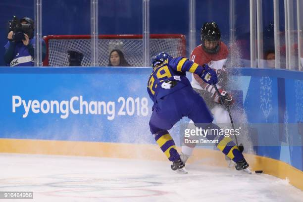 Olivia Carlsson of Sweden and Mika Hori of Japan battle for the puck along the boards in the second period during the Women's Ice Hockey Preliminary...