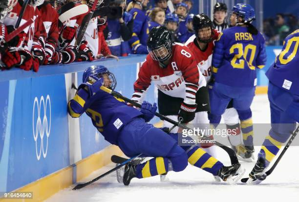 Olivia Carlsson of Sweden falls into the boards as Akane Hosoyamada of Japan looks on in the second period during the Women's Ice Hockey Preliminary...