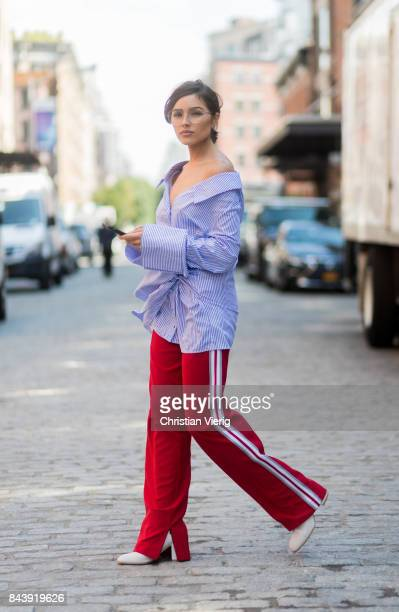 Olivia Culpo is seen wearing a blue white striped button shirt with long sleeves Off White red pants Anderson bell white boots Stuart Weitzman...
