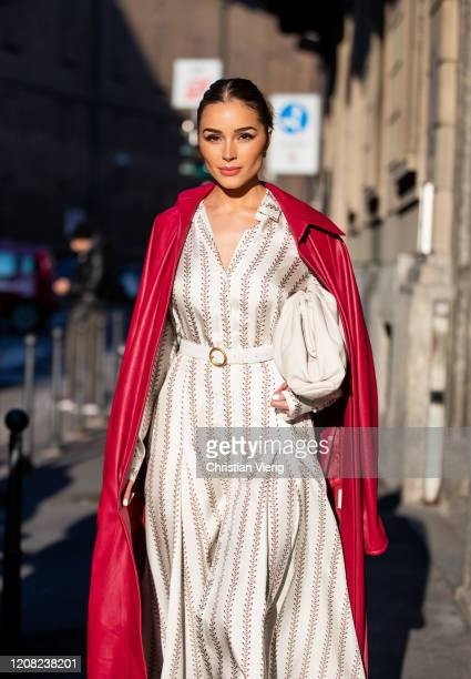 Olivia Culpo is seen wearing belt and bag Bottega Veneta, red coat and overall Gabriela Hearst during Milan Fashion Week Fall/Winter 2020-2021 on...