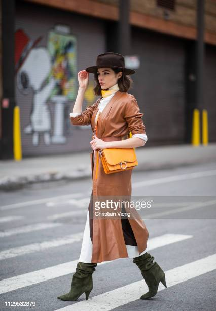 Olivia Culpo is seen wearing Ferragamo bag, Saint Laurent boots, Fendi scarf, Sally LaPointe skirt and top, brown coat during New York Fashion Week...
