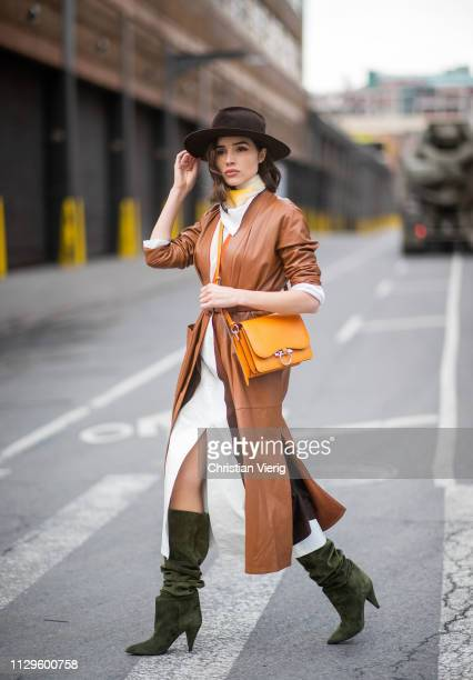 Olivia Culpo is seen wearing Ferragamo bag Saint Laurent boots Fendi scarf Sally LaPointe skirt and top brown coat during New York Fashion Week...