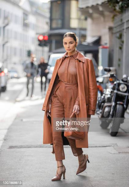 Olivia Culpo is seen wearing rust brown bag, coat, sheer top, pants and heels Tods during Milan Fashion Week Fall/Winter 2020-2021 on February 21,...