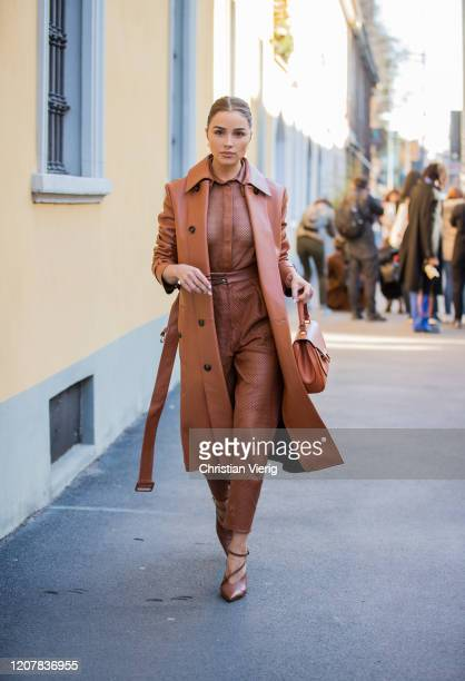 Olivia Culpo is seen wearing rust brown coat and pants, sheer top outside Tods during Milan Fashion Week Fall/Winter 2020-2021 on February 21, 2020...