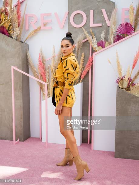 Olivia Culpo is seen wearing yellow jacket and shorts with print and brown belt at Revolve Festival during Coachella Festival on April 14 2019 in La...
