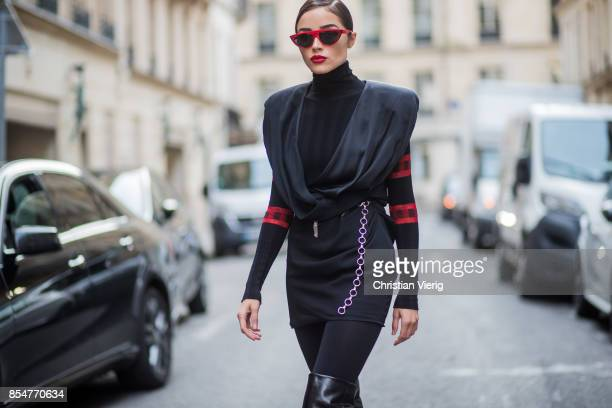 Olivia Culpo wearing a black turtleneck top Aquilano Rimondi a black dress Carmen March with belt Wolford black tights Yves Saint Laurent boots red...