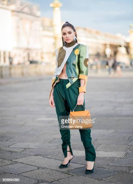 Olivia Culpo wearing Ronald van der Kemp pants and jacket Valextra bag Nina Ricci shoes Jennifer Fisher jewelry seen during Paris Fashion Week...