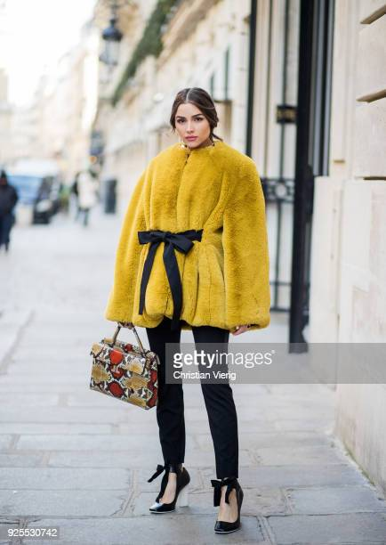 Olivia Culpo wearing total look Lanvin including mustard teddy jacket black pants bag heels with bow is seen on February 28 2018 in Paris France
